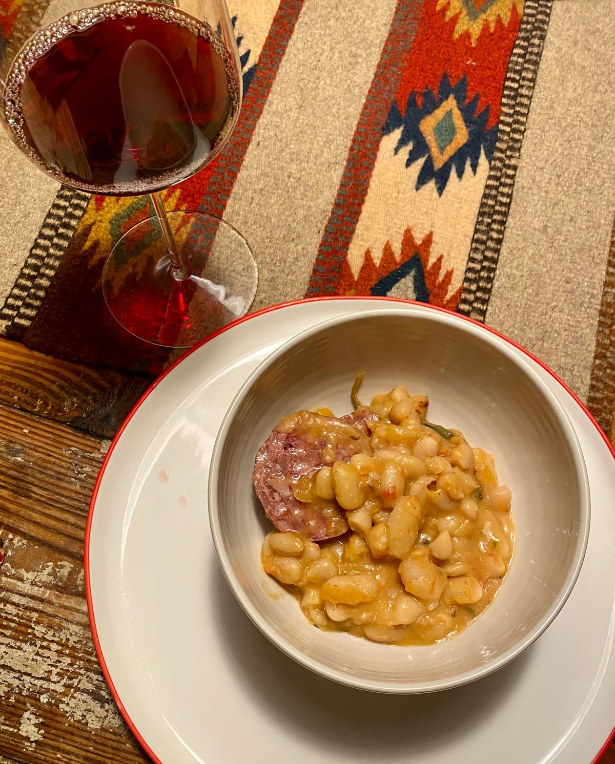 A bowl of white beans and sausage next to a glass of wine