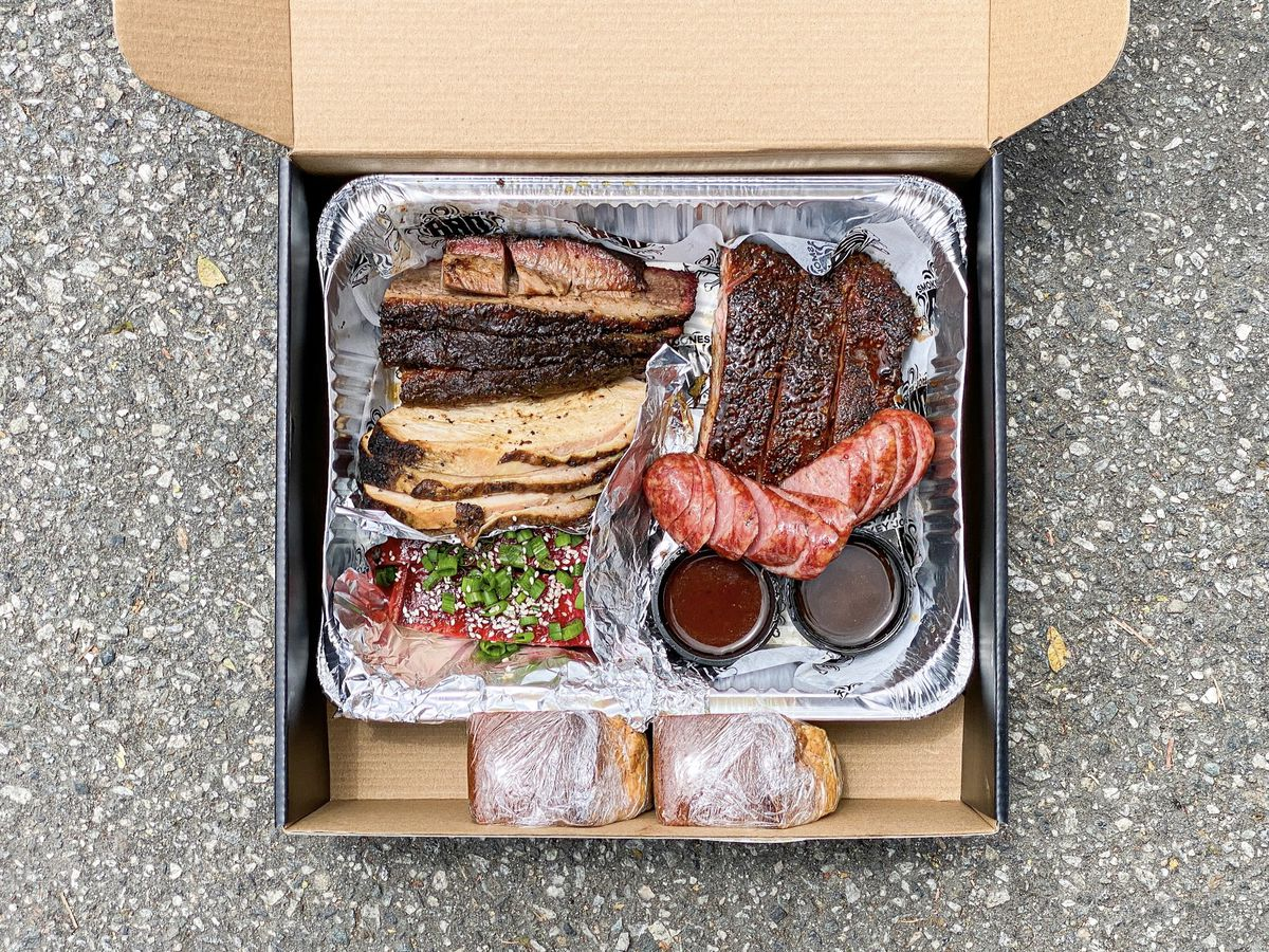 Shown from above, a box of smoked meat sits on a street ready to be consumed.