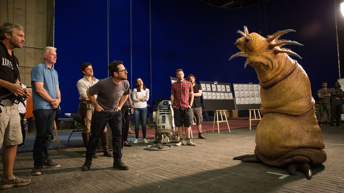 Various cast and crew, including Neal Scanlan and director J.J. Abrams, gather around a large, armless, bug-eyed alien puppet behind the scenes on The Rise of Skywalker.