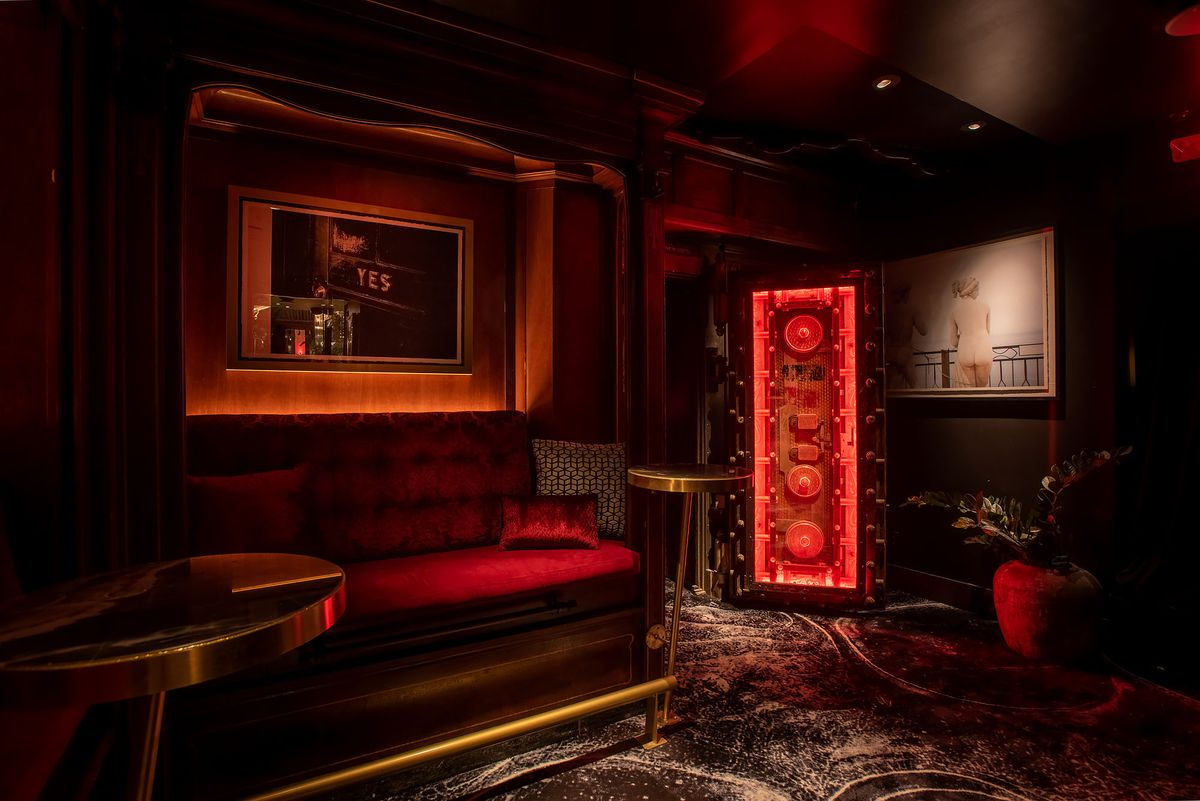 A deep red lounge area with a bank vault door.