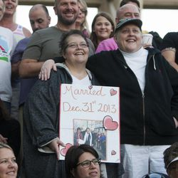 Cheryl Haws, right, holds a sign with her wife, Shelly Eyre, during a same sex marriage celebration at Library Square in Salt Lake City, Monday, Oct. 6, 2014.