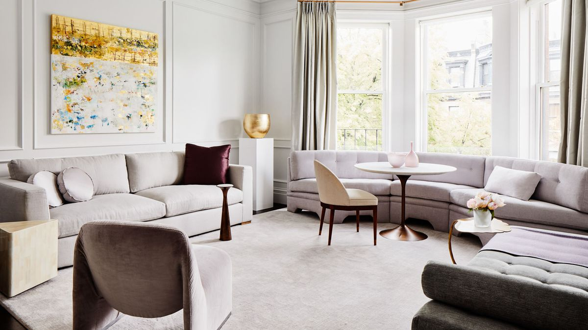 A large, luxurious looking living room with wall-to ceiling-windows. Two dove grey couches meet in the corner of a room where there is a gold sculpture on a white pedestal. There is a small, white cafe table and upholstered chair in front of the left couch creating an additional seating space. Above the right side couch there's a large abstract painting with a gold palette that compliments the sculpture.