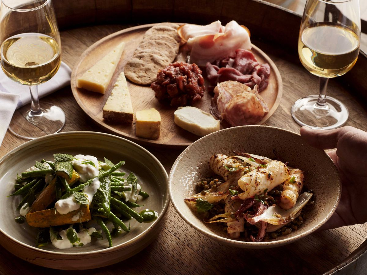 Grilled squid, charcuterie, cheese, and salad with white wine in glasses on a wooden table