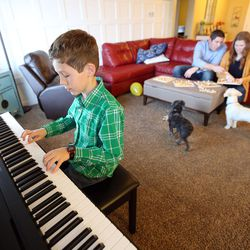 Luke Widdison practices the piano as his parents, Kyle and Emily Widdison, pick up a puzzle at their home in Saratoga Springs, Utah, Friday, Jan. 8, 2016.