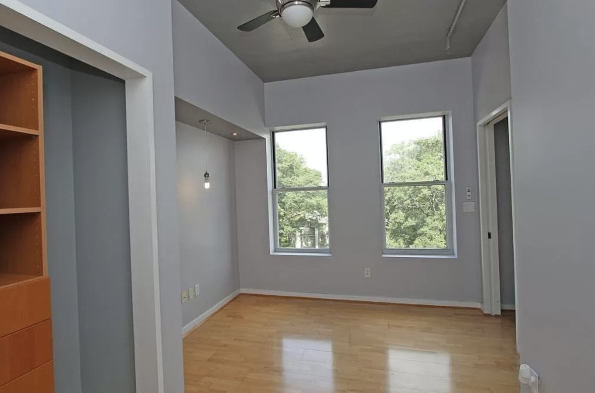 Empty bedroom with cabinet on the left.