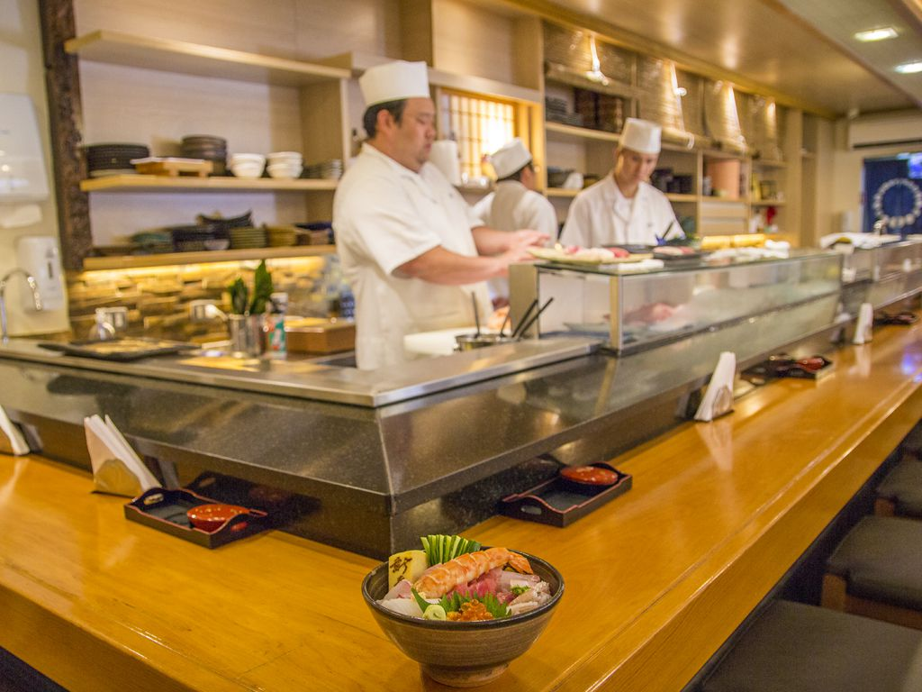 A bowl of chirashi overflowing with various pieces of fish sits on an L-shaped sushi counter while sushi chefs work behind the bar.