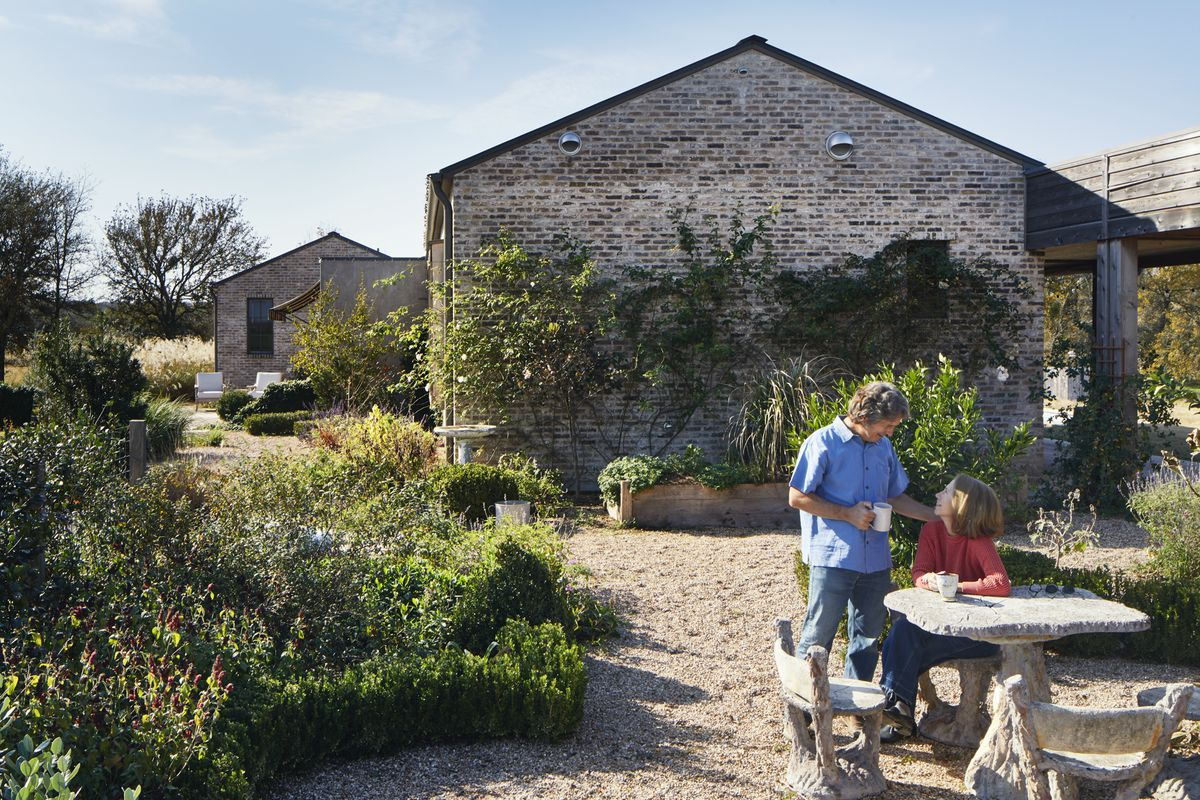 The owners sit and stand around a faux bois table and chairs in the garden. The plantings are naturalistic, and pea gravel covers the ground.