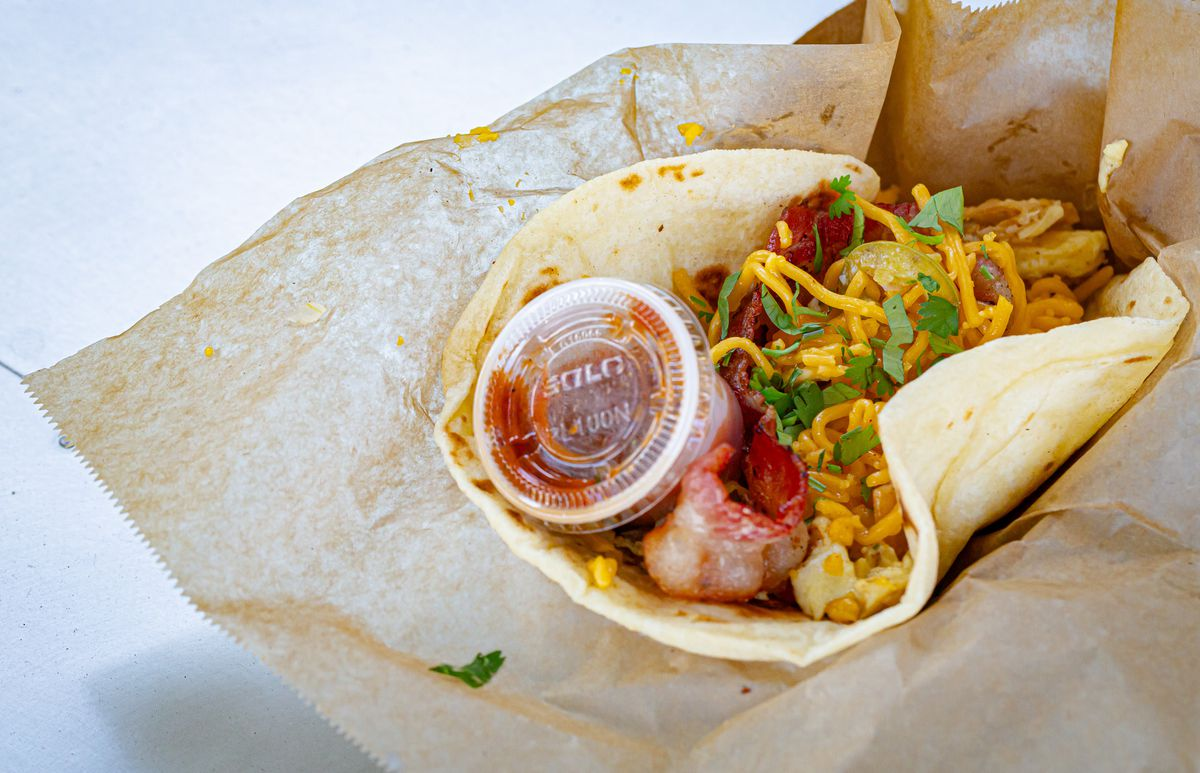 Bacon taco in flour tortilla filled with migas, twice-fried beans, cheese, and bacon