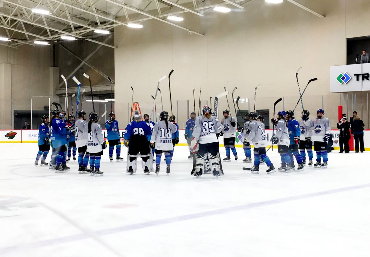 Two hockey teams with their sticks raised at center ice.