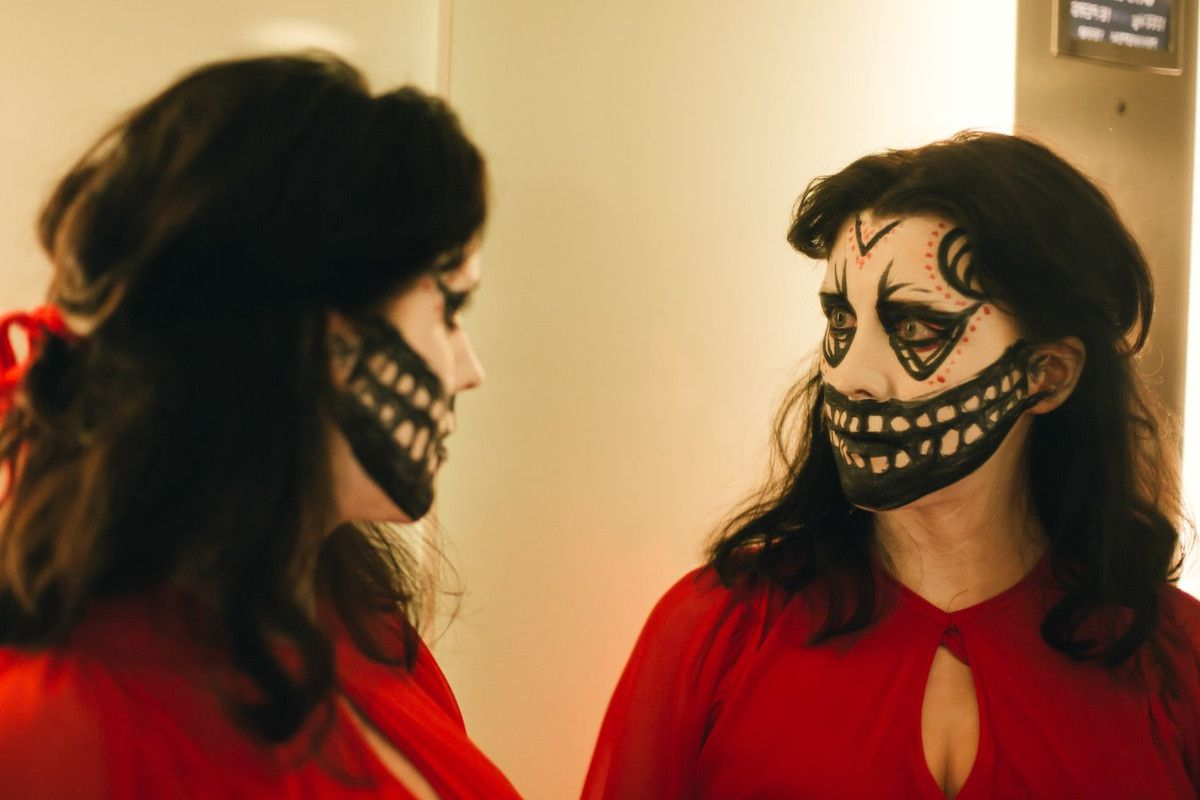 a woman in skull makeup looks at herself in the mirror
