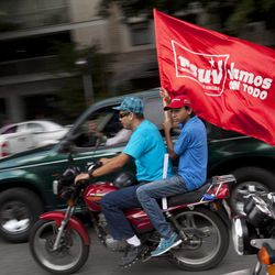 """A supporter of Venezuela's President Hugo Chavez holds a flag that reads in Spanish: """"We're going all out,"""" while taking part in a campaign caravan through the streets of Caracas, Venezuela, Friday, Sept. 28, 2012. Venezuela's presidential election is scheduled for Oct. 7."""