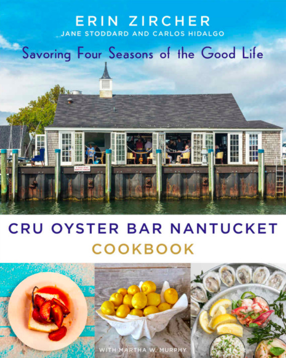 A cookbook cover features the exterior of a waterfront restaurant on a dock as well as several summer-y dishes of food.
