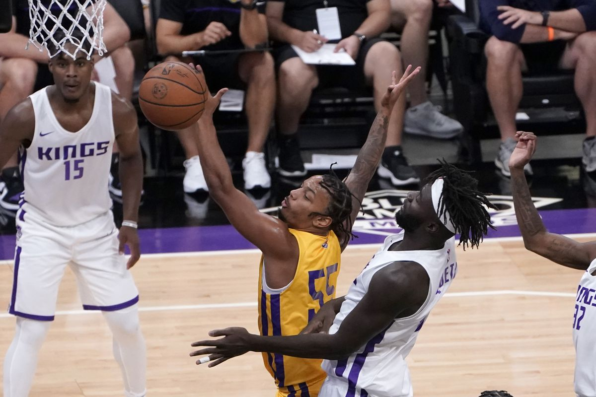 Los Angeles Lakers guard Justin Robinson, left, reaches for the ball in front of Sacramento Kings center Neemias Queta.