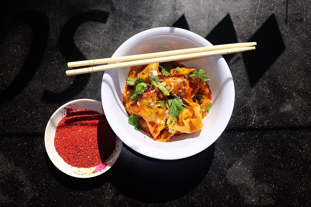 A small bowl is filled with wontons in a spicy red oil, garnished with scallions, with a small bowl of red sauce to the side.
