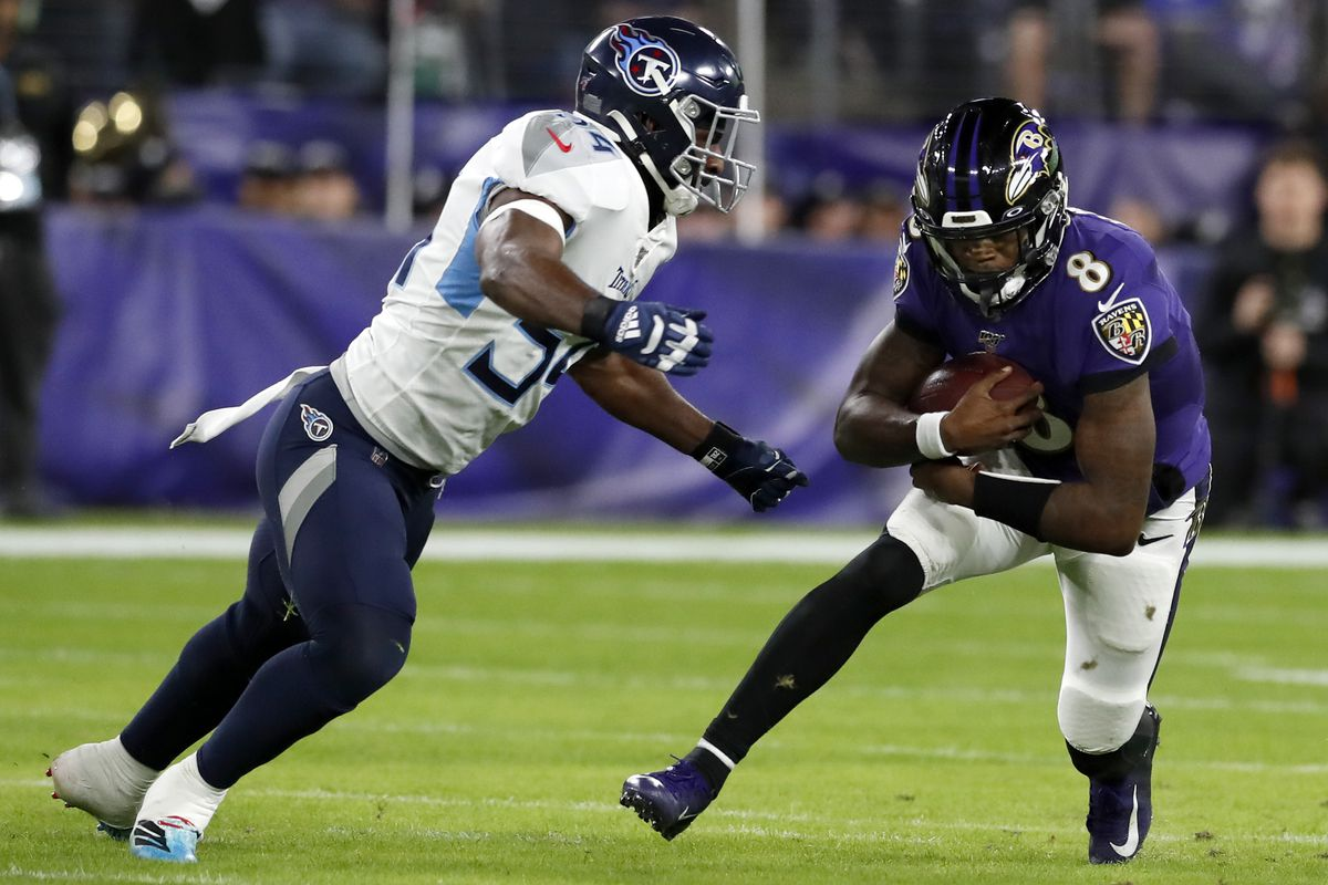 Quarterback Lamar Jackson of the Baltimore Ravens carries the ball against Rashaan Evans of the Tennessee Titans during the AFC Divisional Playoff game at M&T Bank Stadium on January 11, 2020 in Baltimore, Maryland.