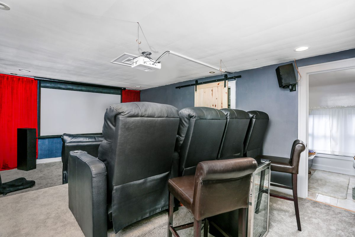 Two rows of three black leather seats face a white screen.