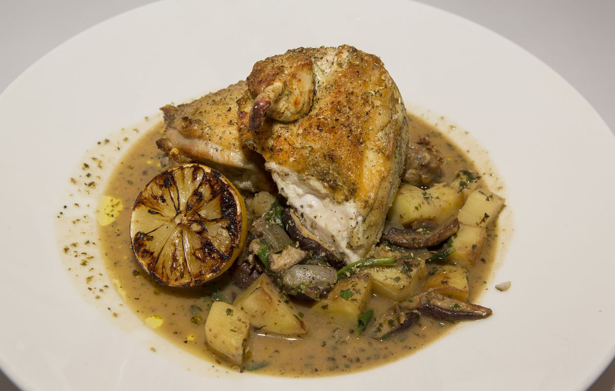 A plate of chicken with lemon and potatoes in sauce.
