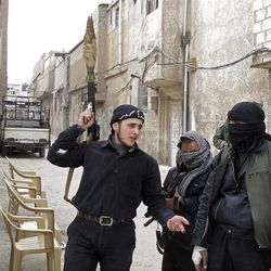 In this Sunday, April 1, 2012 photo, Free Syrian Army fighters are seen in a neighborhood of Damascus, Syria.