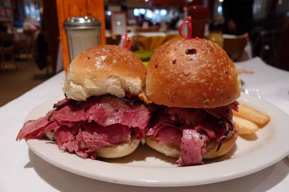 Two prim little pastrami sandwiches on onion rolls on a white plate.