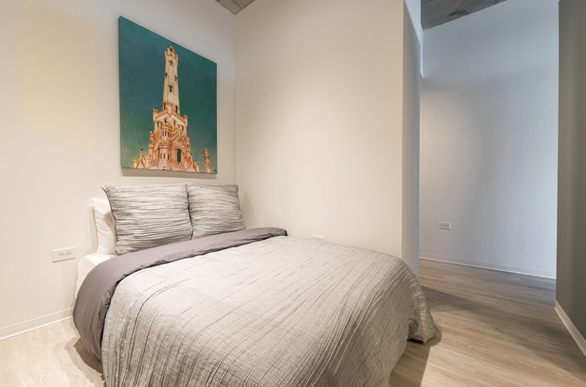 A bedroom with a separating wall. There is art above the bed.
