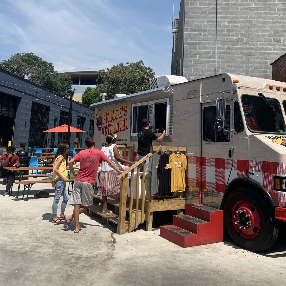 Prince's hot chicken food truck, a red umbrella and patio tables, short line of people