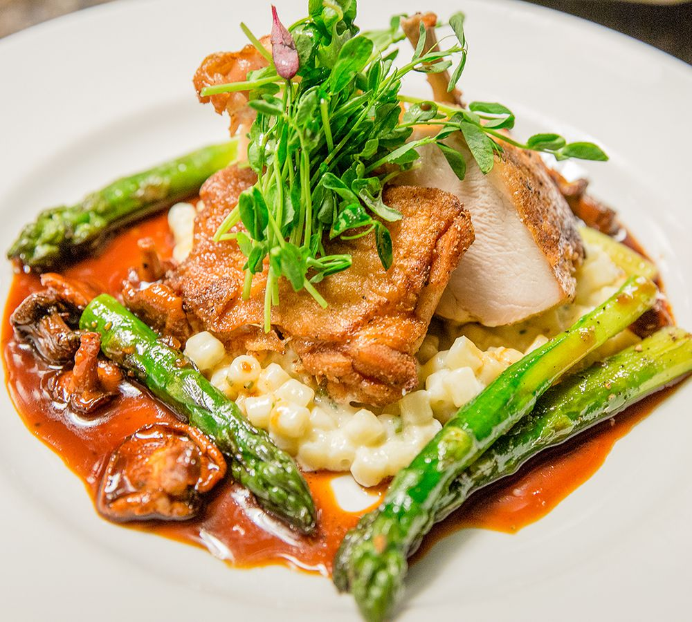 Closeup of an elegantly plated chicken dish with asparagus, mushrooms, and a brown sauce surrounding the chicken on a white plate.