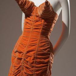 Jean Paul Gaultier, orange shirred velvet dress with cone bust and back lacing, 1984, France. The Museum at FIT.