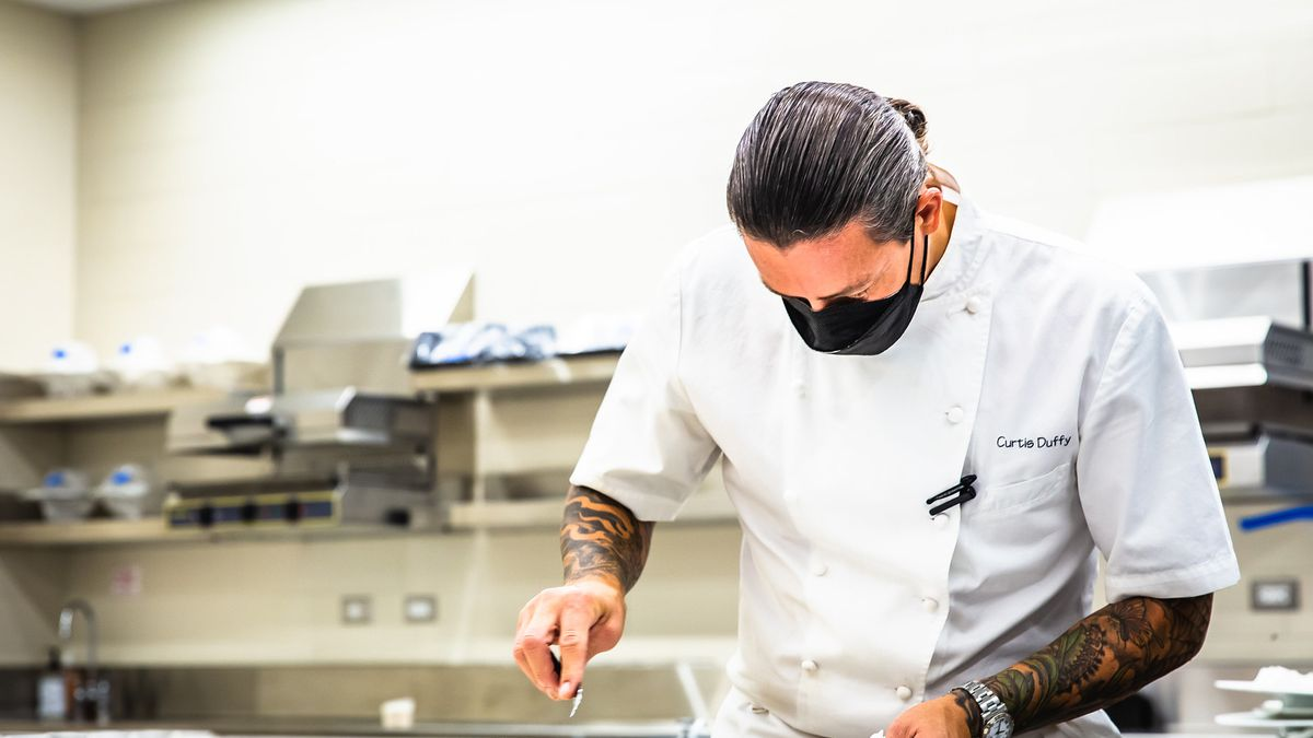 A masked chef in a kitchen.