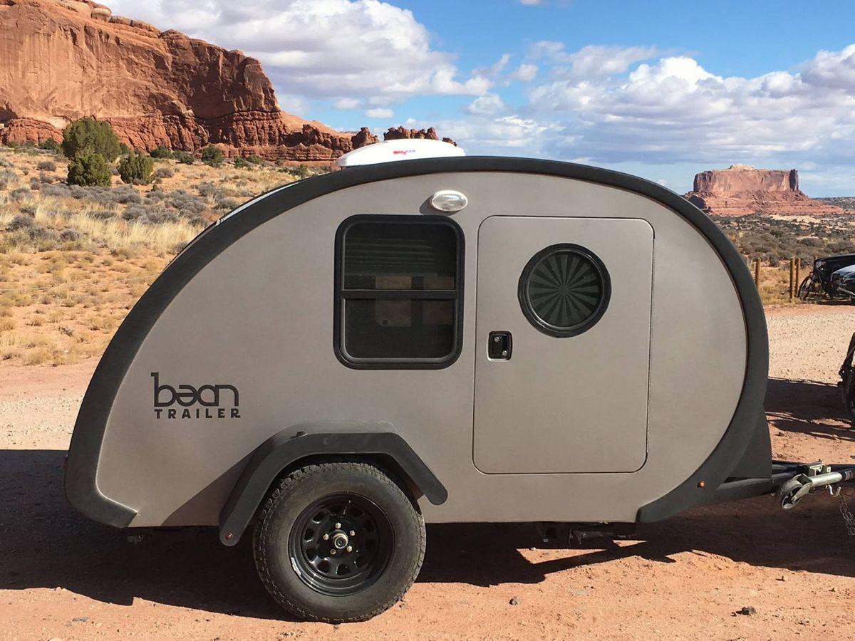 A teardrop trailer sits in the desert