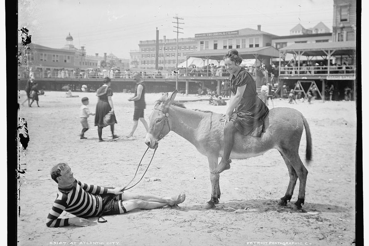 A black and white photo of a woman riding a donkey on the beach with a man lying on the beach in Atlantic City.