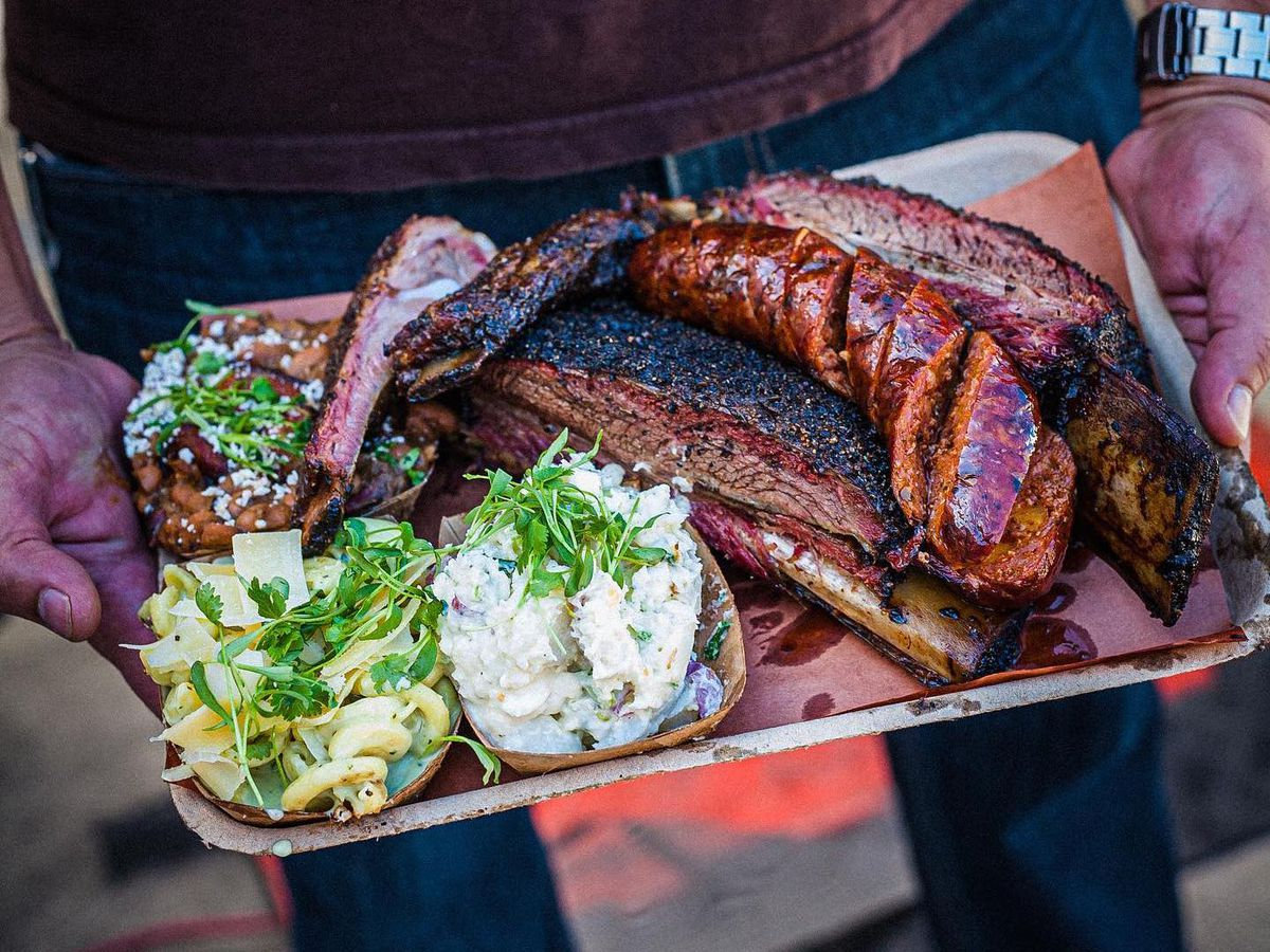 A tray of barbecue and sides held in two hands from above.