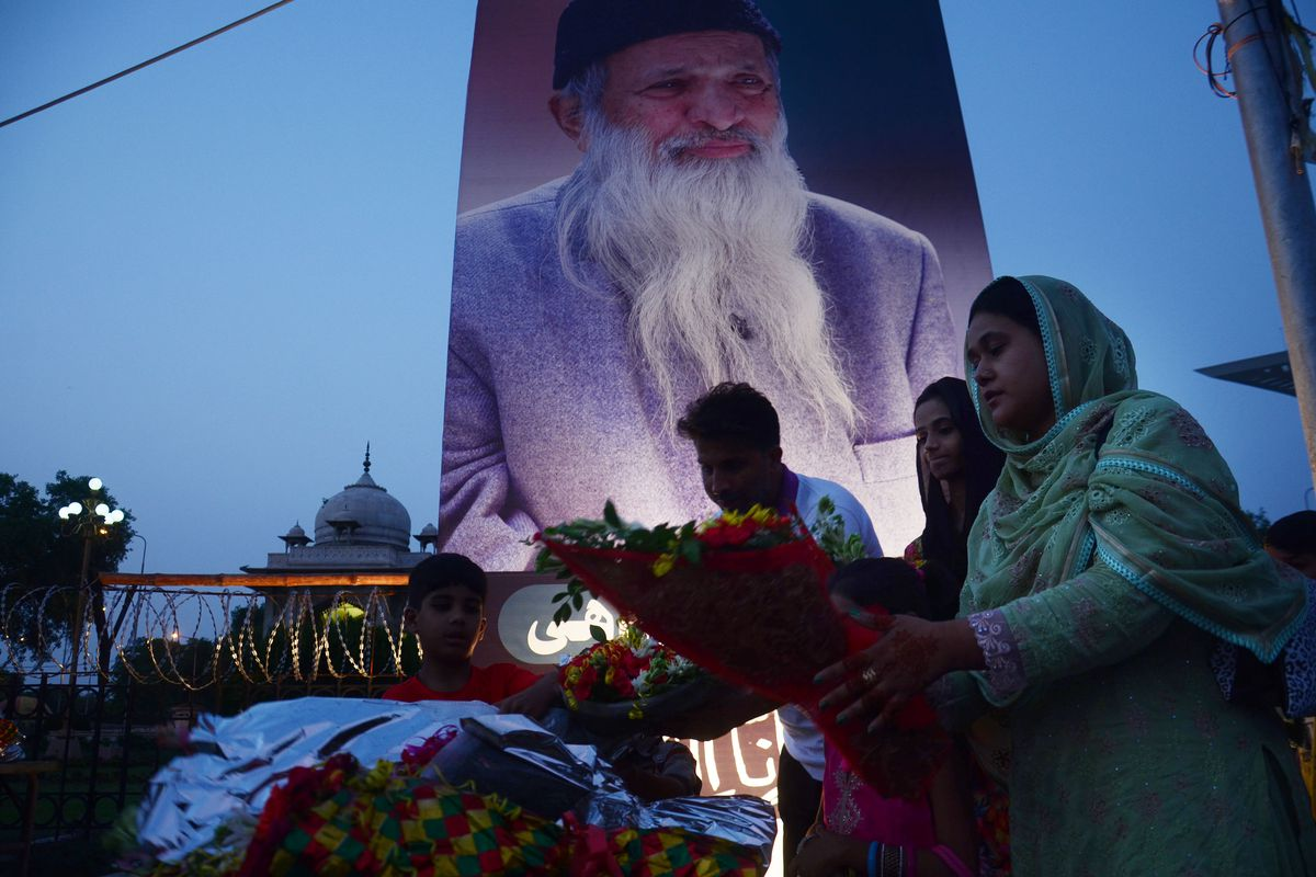Pakistani people offer flower bouquets in front of portrait of the Abdul Sattar Edhi