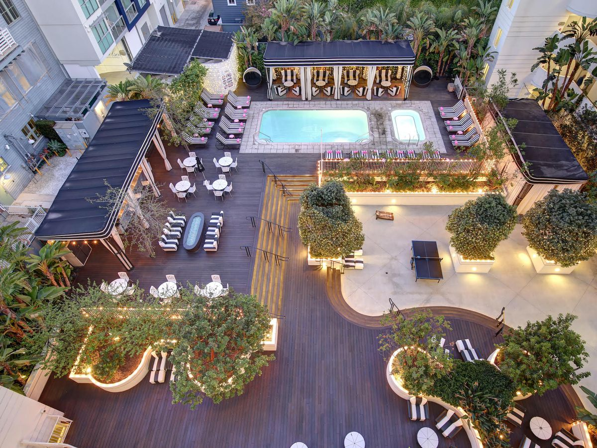 A view from above of a hotel pool deck with cabanas.