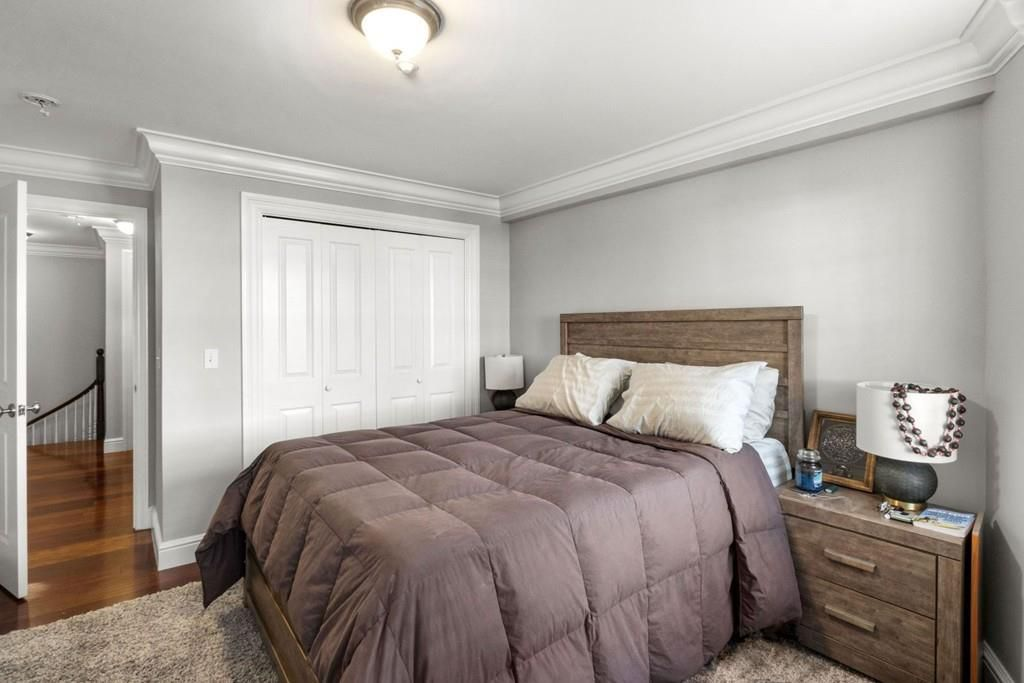 A bedroom with a bed, and there's a stairwell visible outside the open door.