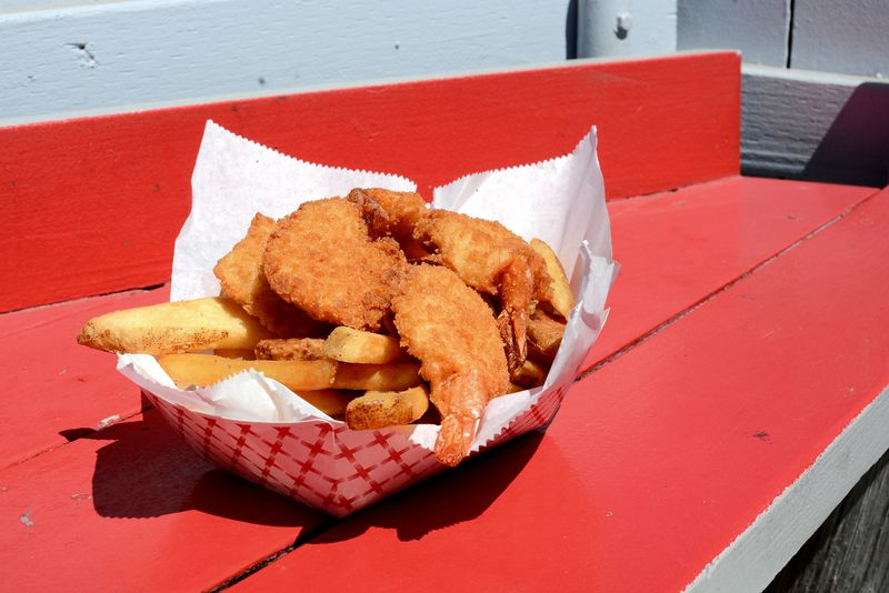 A paper-lined basket of golden shrimp and French fries set on a table painted red.