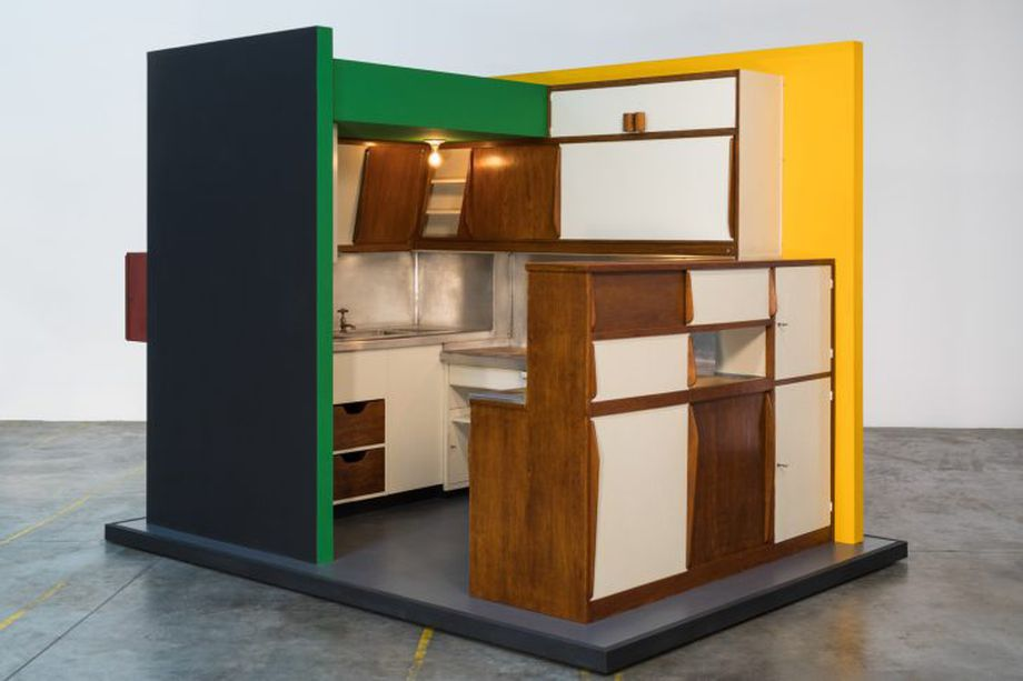 A brightly colored modular kitchen design that has all appliances and cabinets built into a tiny compact space.