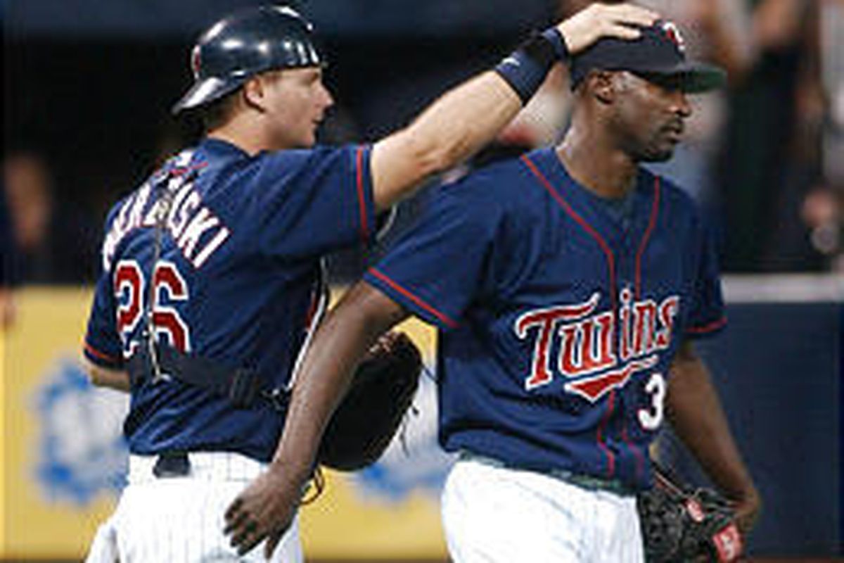 Twins catcher A.J. Pierzynski gives pat on head to reliever LaTroy Hawkins after win over White Sox.