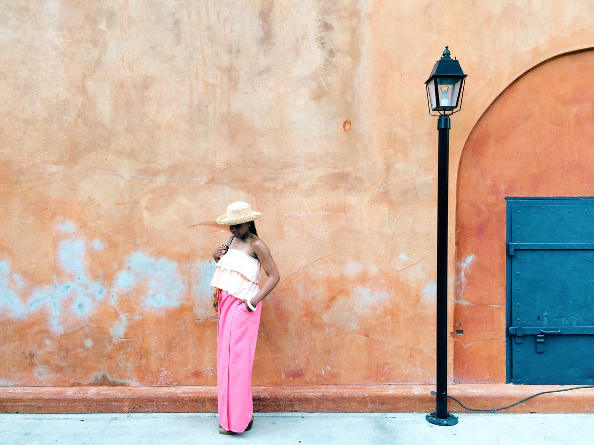 A woman wearing a hat in pink and orange against and orange stucco wall, near a lamp post.