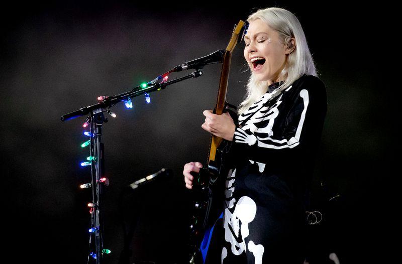 Phoebe Bridgers onstage playing guitar and singing.
