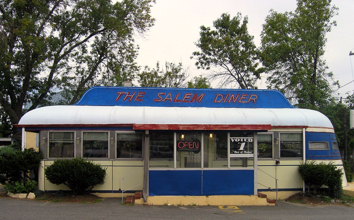 Front view of the exterior of the historic Salem Diner, a classic-looking diner car. The signage is blue and red and the car is white.