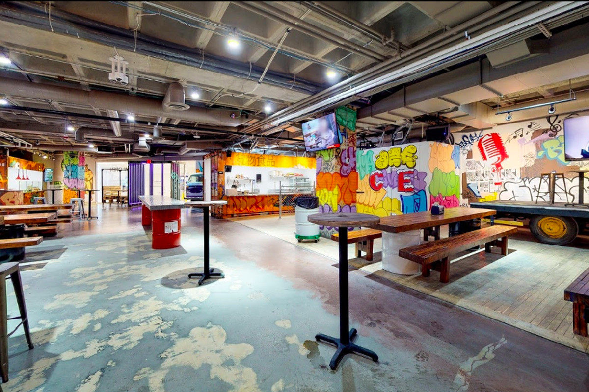 A wharehouse like dining room with tall tables and a room decorated with shipping containers and graffiti