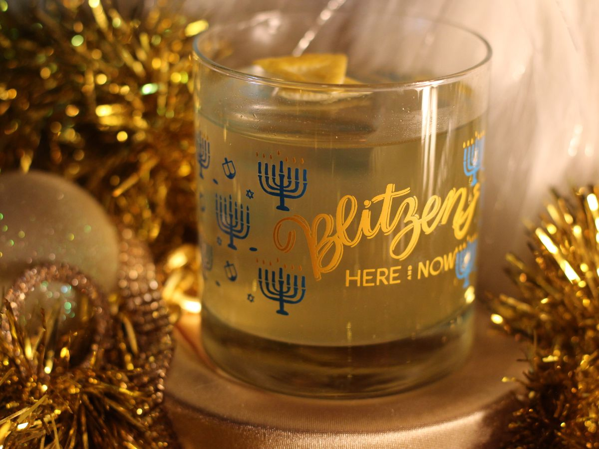 A mostly clear cocktail with a run of citrus sits in a holiday-themed decorative set.