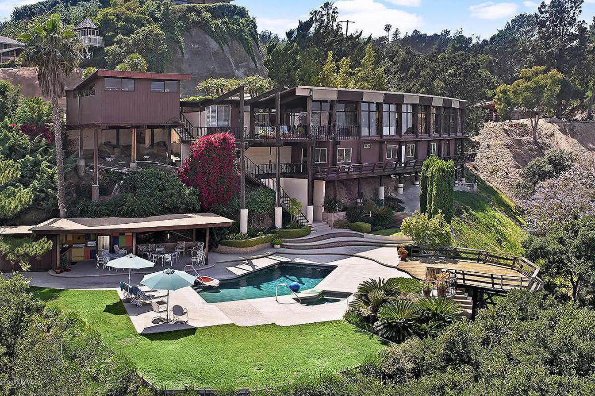 Exterior shot of back of long wood-frame house set onto hillside, with a pool, patio, yard, and deck below it.