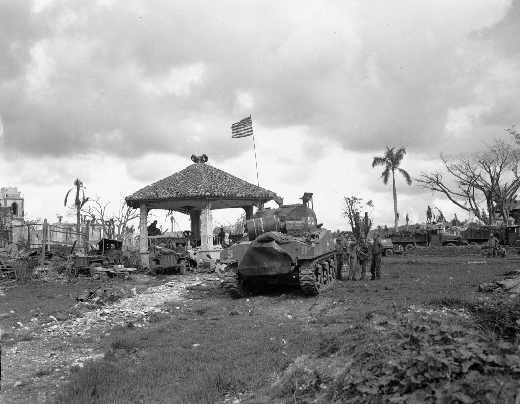 """This August 1944 file photo shows an American flag atop the first U.S. tank to lead the push to Agana, capital of Guam. The small U.S. territory of Guam has become a focal point after North Korea's army threatened to use ballistic missiles to create an """"e"""