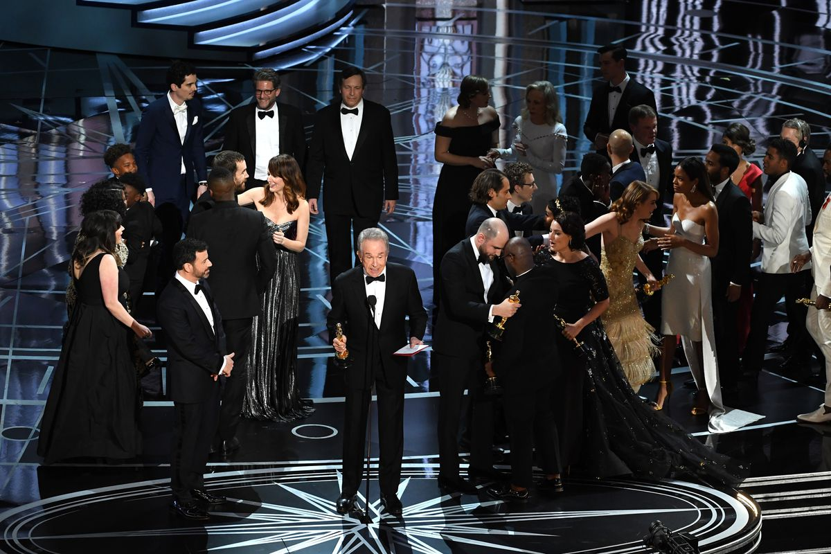 Warren Beatty explains the Oscars mix-up while Faye Dunaway (top right) recedes into the literal shadows (GettyImages)