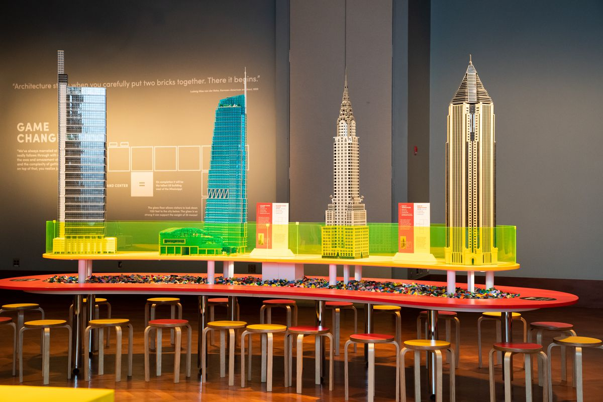 Four more skyscrapers built out of Legos. They're protected by a low green glass wall.