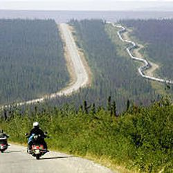 A group of motorcyclists drives the 400-mile Dalton Highway near the Arctic Circle in Alaska. The trans-Alaska oil pipeline is at right.