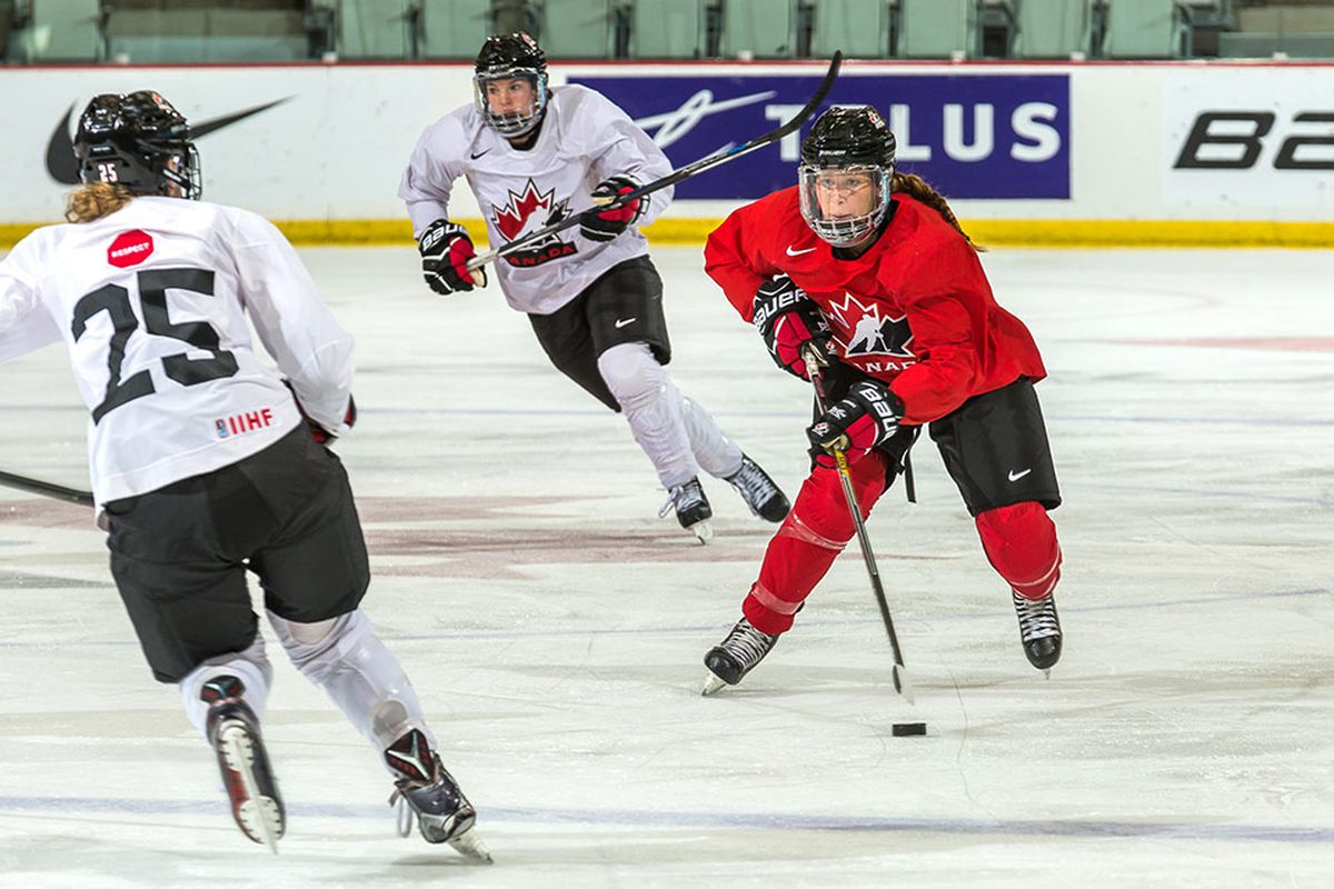 Two hockey players in white jerseys defend against a skater in red during a Hockey Canada intrasquad game.
