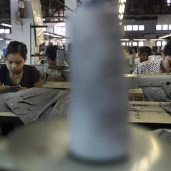 In this photo taken Saturday, April 21, 2012, young laborers work at a garment factory in Yangon, Myanmar. On Monday, April 23, 2012, the European Union confirmed it was suspending most of its sanctions against Myanmar to reward the country's recent wave of political reform. The suspension of trade sanction could help revive the nation's industries, restoring some of the 80,000 garment industry jobs lost here over the past 10 years.