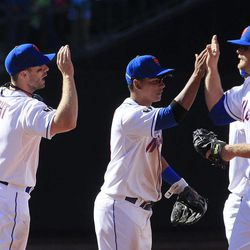 New York Mets' Daniel Murphy, right, Ruben Tejada, center, and David Wright, left, congratulate one another after the Mets' 7-5 win over the Atlanta Braves in a baseball game Sunday, April 8, 2012, in New York.